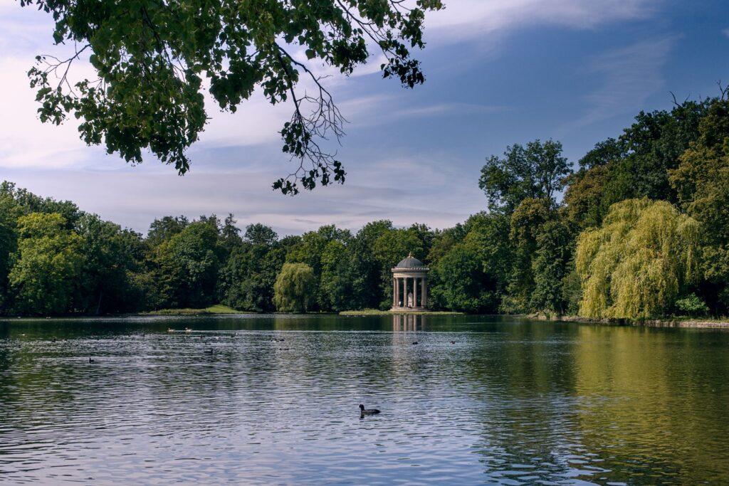 Badenburgersee mit kleinem Tempel am gegenüberliegendem Ufer und einem schwimmenden Vogel auf der Wasserobefläche