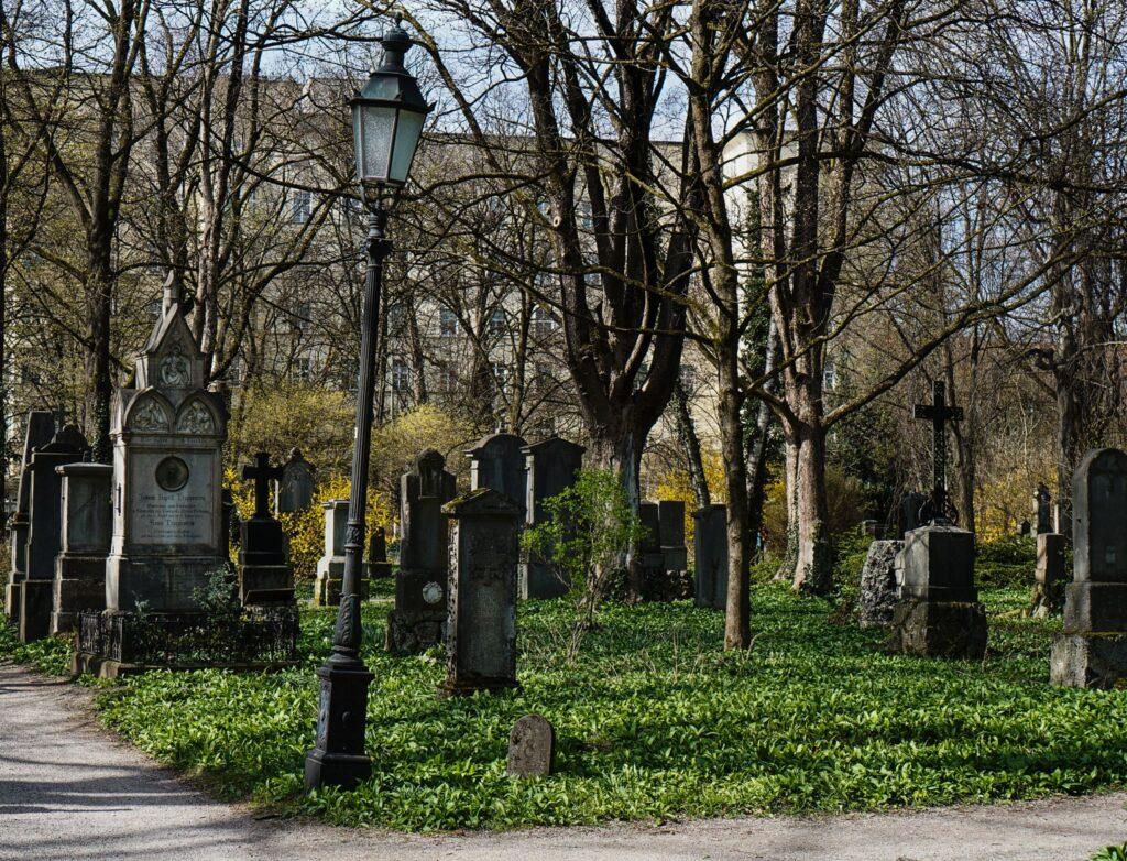 Gräberfeld auf dem Alten Südfriedhof in München mit schiefer Laterne