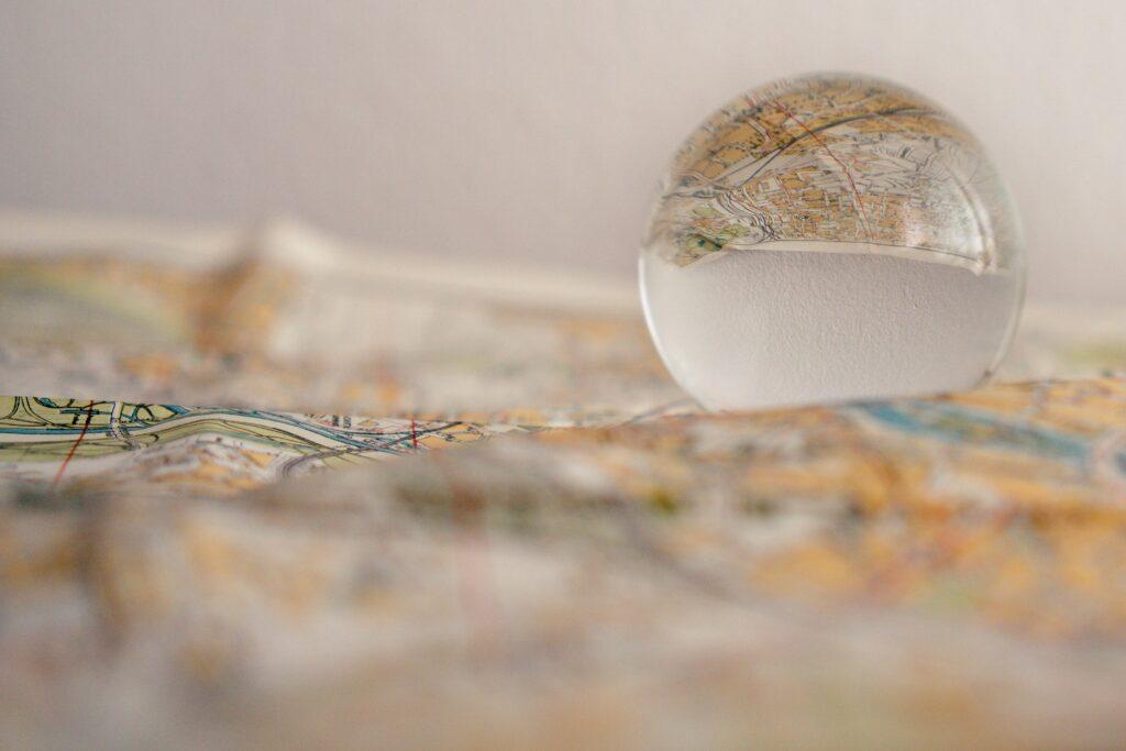 München anders entdecken: Stadtplan, der sich in einer Glaskugel spiegelt