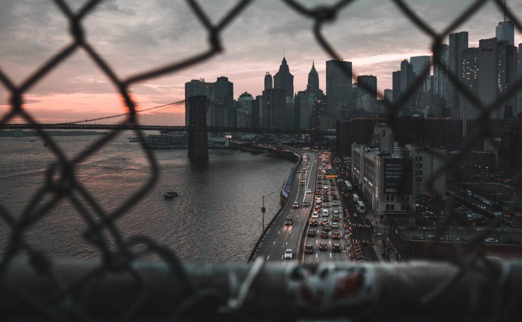 Shiny Objects auf der Uferstraße im Dämmerlicht mit Skyline von New York und Verkehr mit glitzernden Lichtern